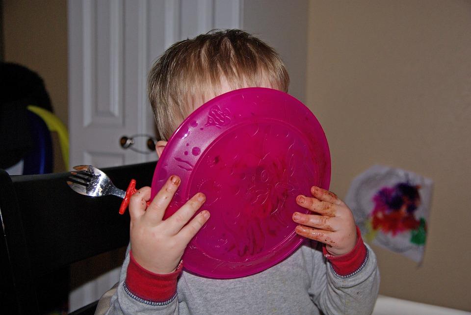 Kind hält sich Teller vor das Gesicht, um ihn abzulecken.