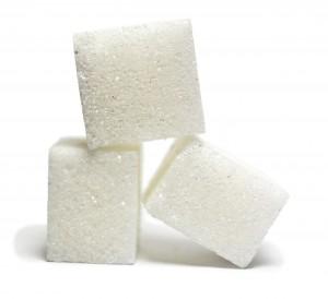 Drei Zuckerwürfel vor weißem Hintergrund.