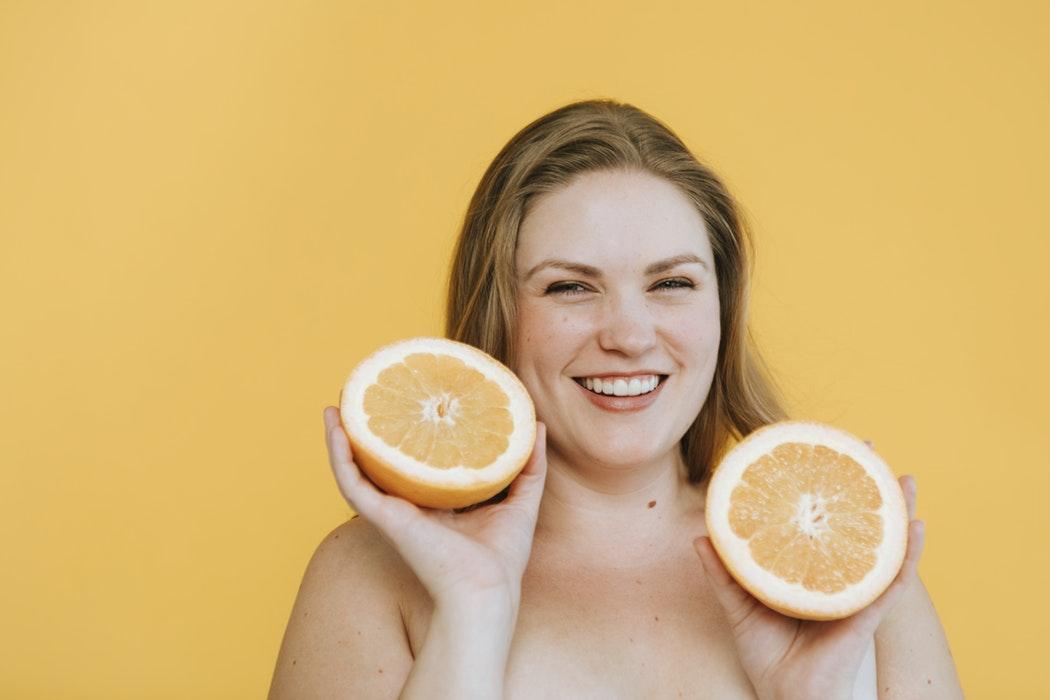 Molllige Frau hält zwei Grapefruit-Hälften in die Kamera, lacht fröhlich.
