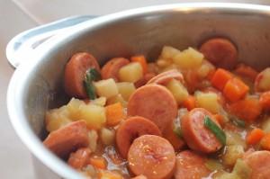 Topf mit Kartoffeleintopf und Würsten.