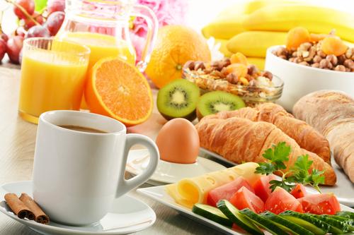 Frühstückstisch mit Kaffee, Obst, Ei, Croissant, Müsli