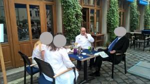 Alfons Schuhbeck am Tisch, drei Personen, Gesichter unkenntlich