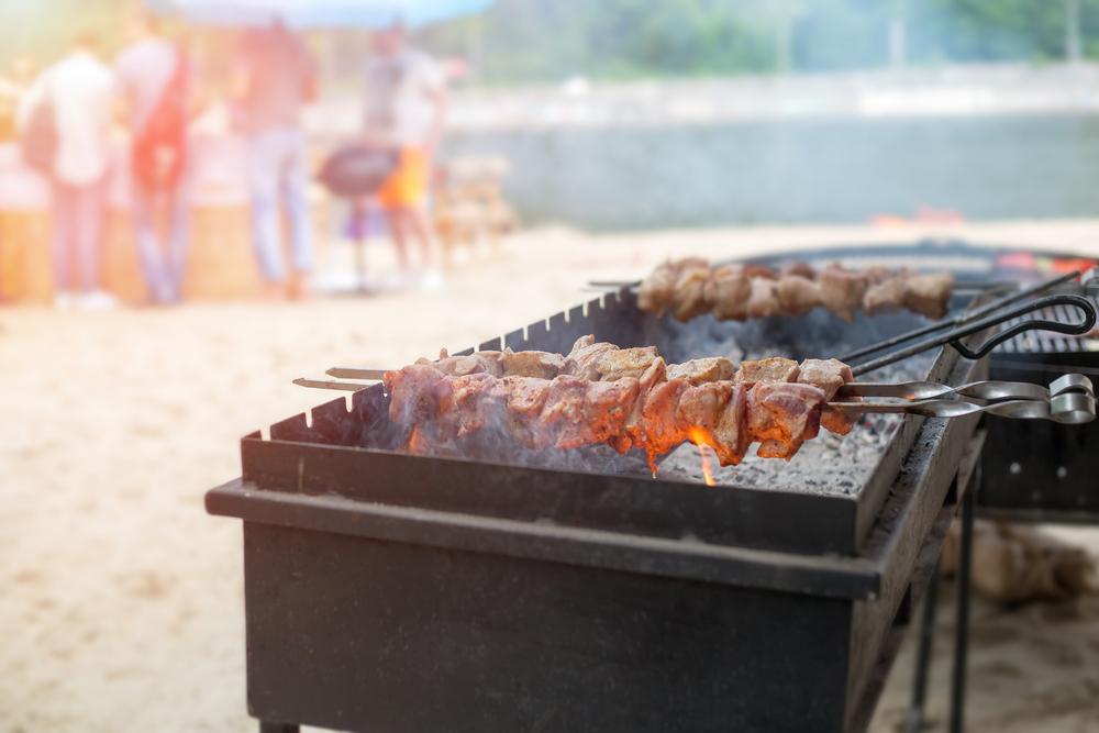 Grill mit Schaschlik-Spießen, im Hintergrund unscharf Strand und Leute
