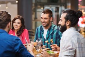 Mann mit Männerdutt sitzt mit anderen beim Essen
