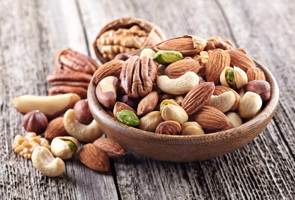 Schale nah mit gemischten Nüssen auf Holztisch, darunter Mandeln, Cashew, Walnüssen, Pekan, Pistazien