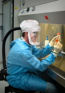 Forscher in Schutzkleidung an Bank, Mikrobiologe