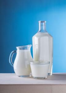 Schale, Kännchen und Flasche Milch vor blauem Hintergrund