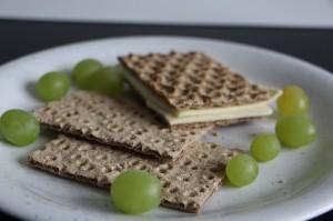 Teller mit Knäckebrot, Käse und Weintrauben