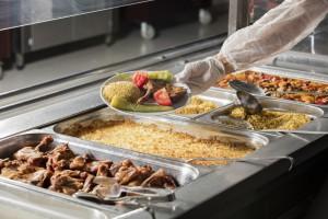 Essensausgabe, Wannen mit verschiedenen Gerichten, Hand präsentiert Teller mit Gemüse, Reis und Fleisch