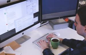 Mann vor Bildschirm und Tastatur, mit Tasse Kaffee
