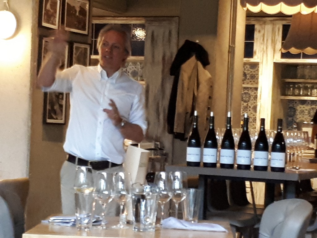 Mann steht und redet, im Hintergrund Weinflaschen