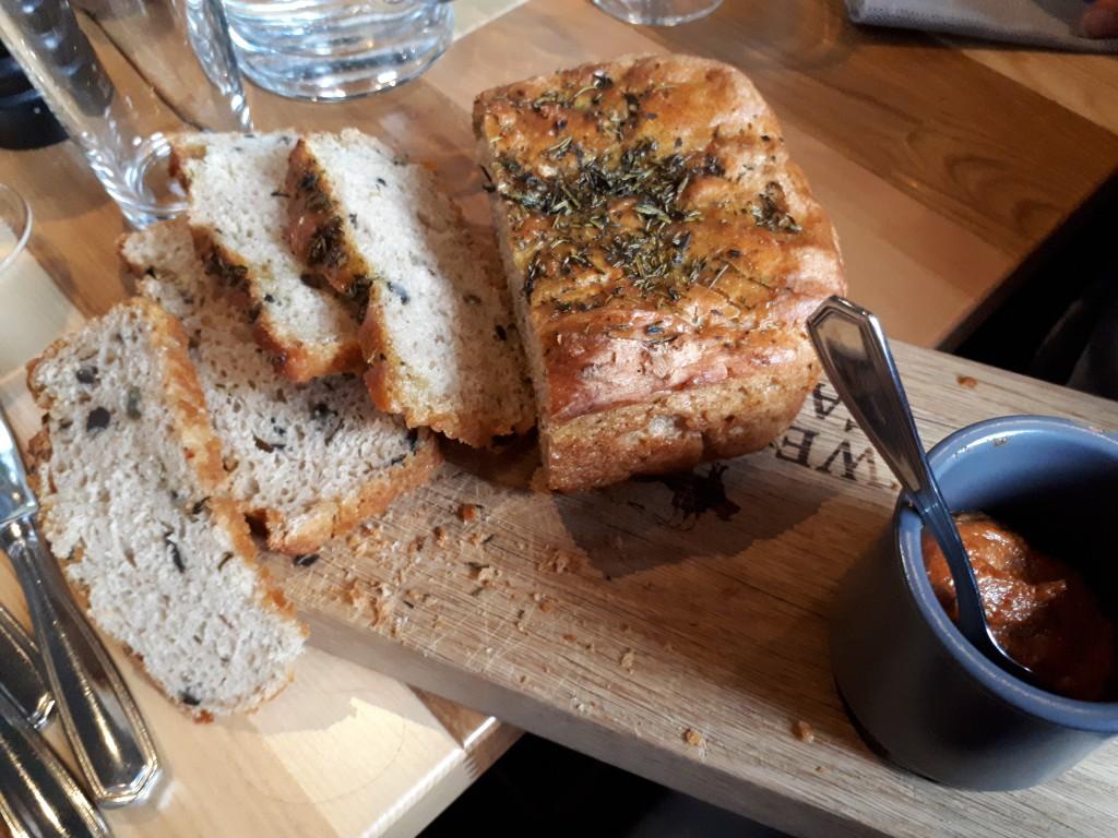Brett mit Brot, Kräuterdecke, Topf mit Pesto