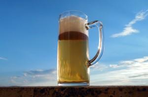 Glaskrug mit Bier vor blauem Himmel