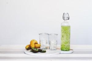 Trinkflasche, Wasser, grün gefärbt, zwei Becher, Obst auf Tisch
