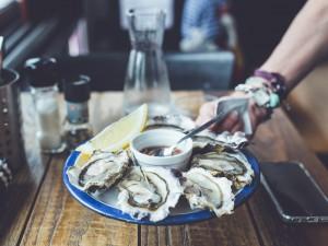 Hand hält Teller mit geöffneten rohen Austern