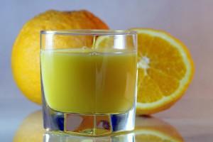 Glas Orangensaft, zwei Orangen im Hintergrund
