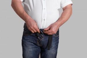 Mann mit dickem Bauch versucht, Jeans zu schließen