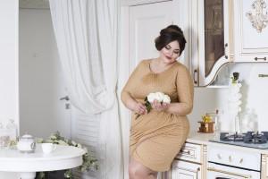 Übergewichtige Frau posiert in braunem, elegantem Kleid in schöner Landhausküche