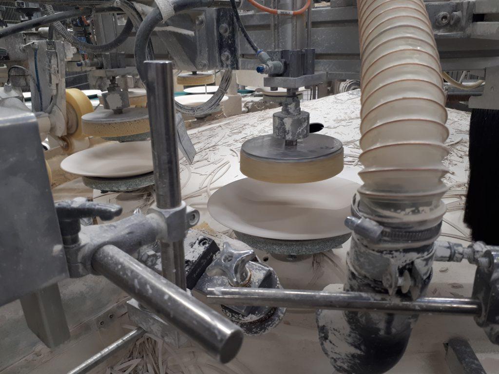 Maschine, rohe, unglasierte Teller stehen auf Scheiben, Schlauch, Polierkopg