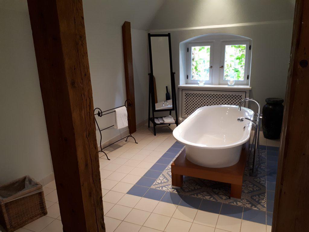 Badezimmer: freistehende Badewanne, blaue Fliesen, alte Holzbalken, Spiegel
