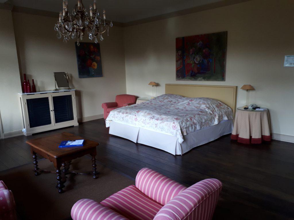 Edles altes Zimmer, Kronleuchter, Sessel, Bett mit geblümter Decke