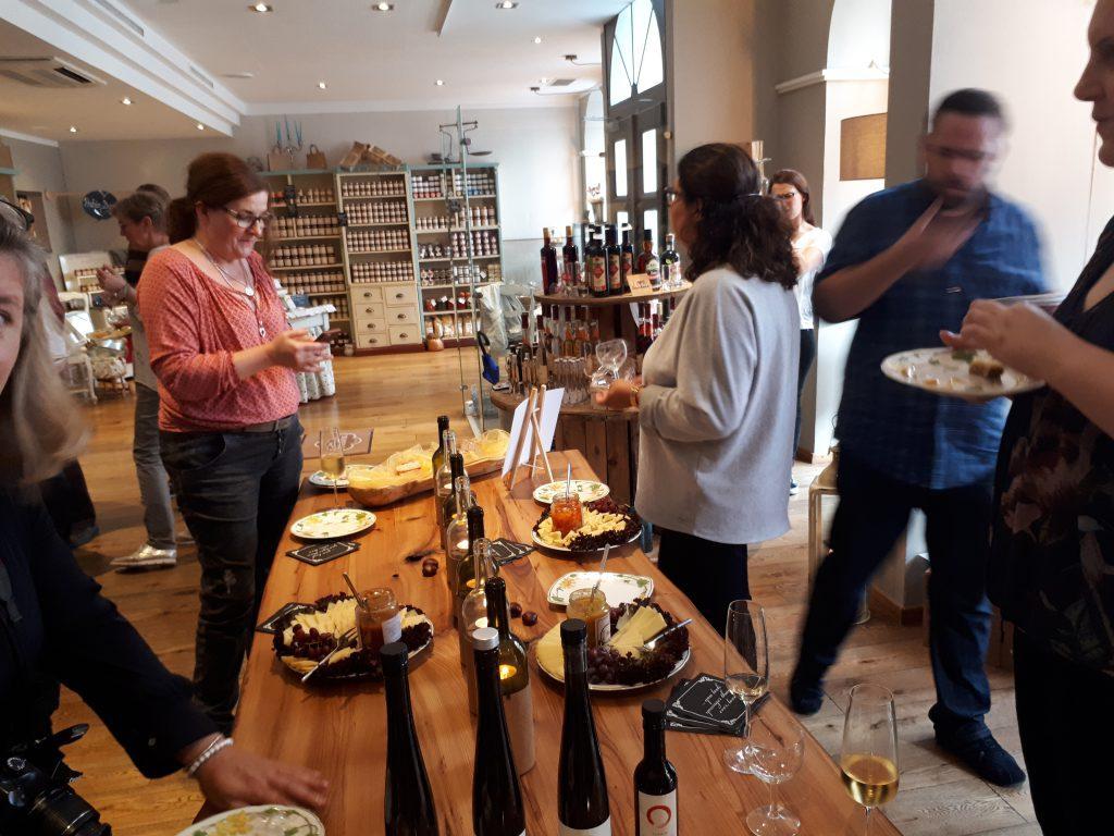 Blick in den Laden: Tisch, Käseplatten, Flaschen und Leute die essen