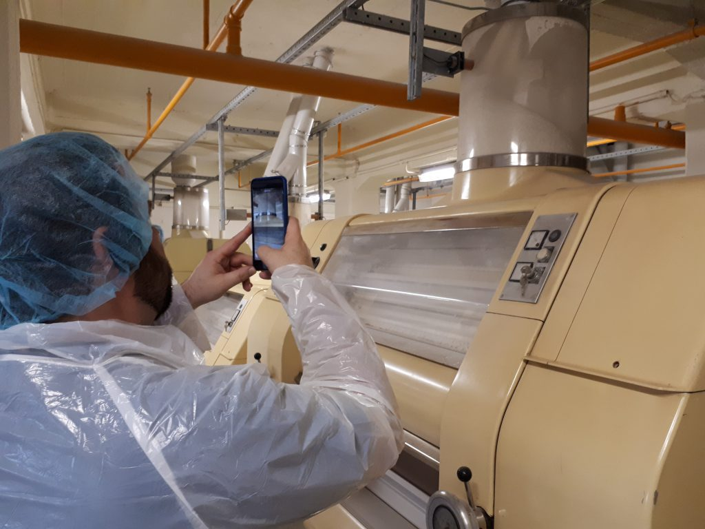 Mann in Schutzkleidung mit Haube fotografiert Maschine (Mahlmaschine, Siebmaschine) in Mühle, innen
