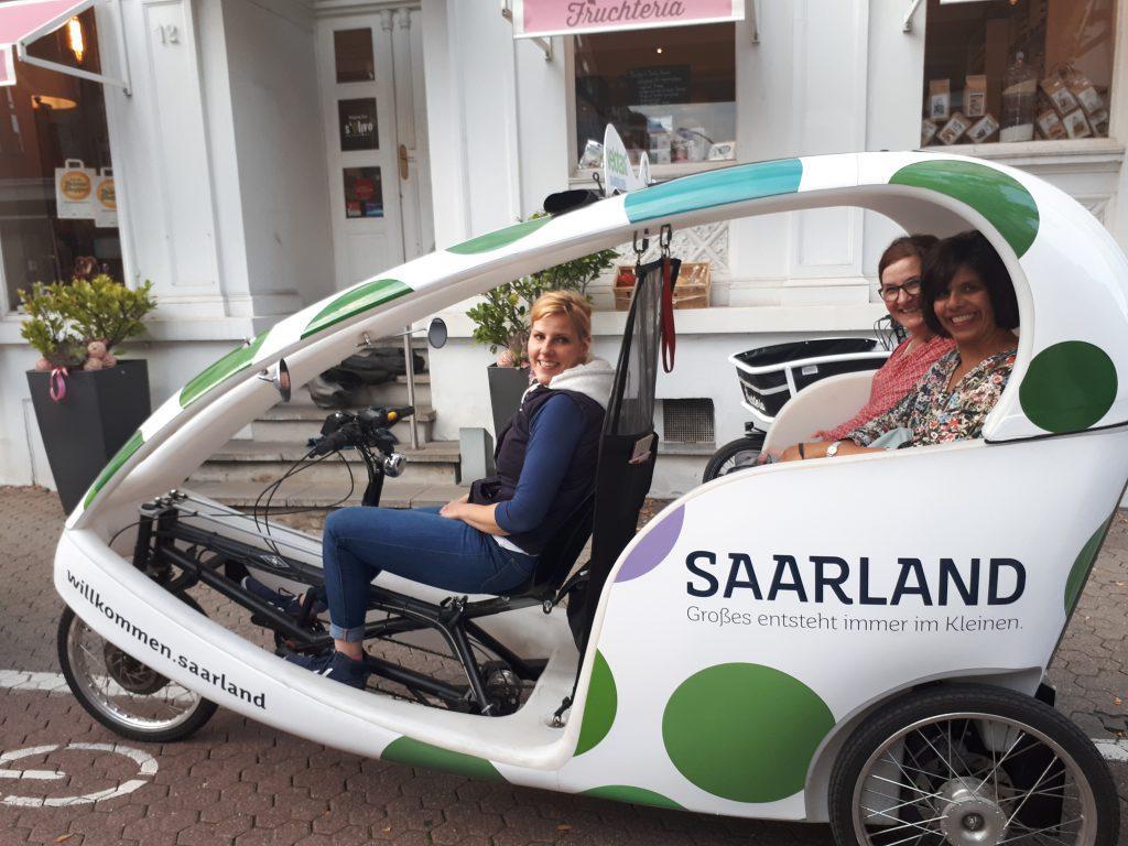 "Radrikscha, Aufschrift ""Saarland"", Fahrerin, zwei Fahrgäste"