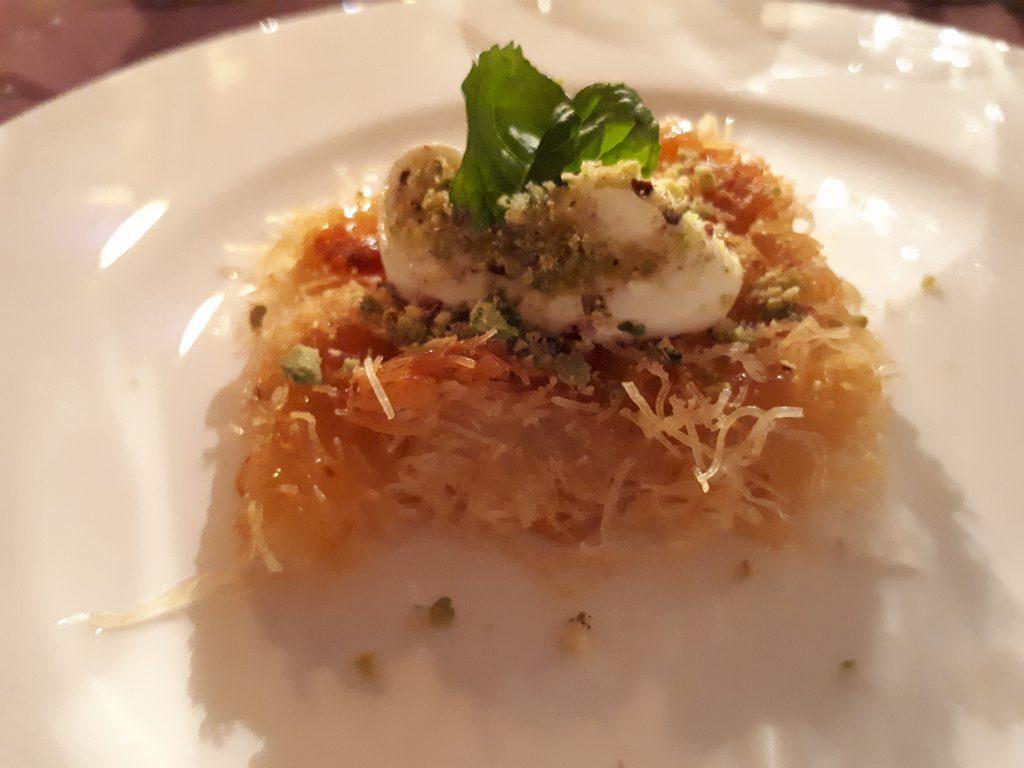 Dessert aus Fadennudeln, Sirup, Mascarpone mit Dekoration Pfefferminzblatt, nah