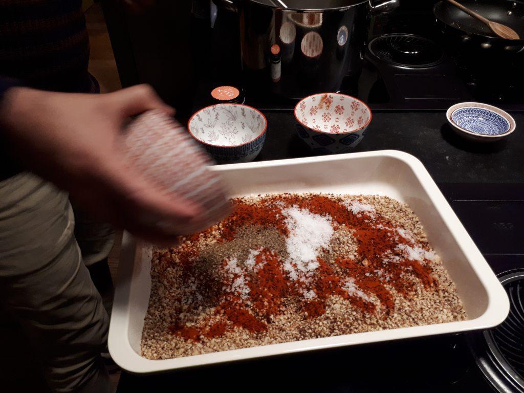 Hand schüttet aus Schale Gewürz in Pfanne mit Nussmischung und Chilipulver, rot