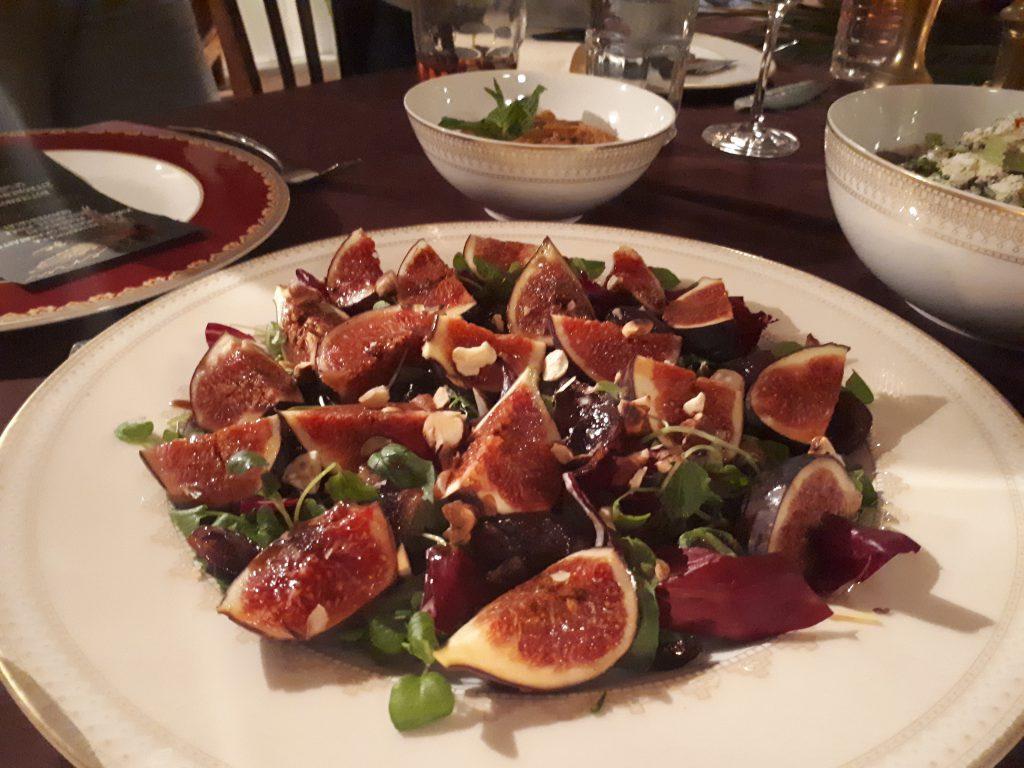 Teller mit Feigenvierteln, Salat, nah