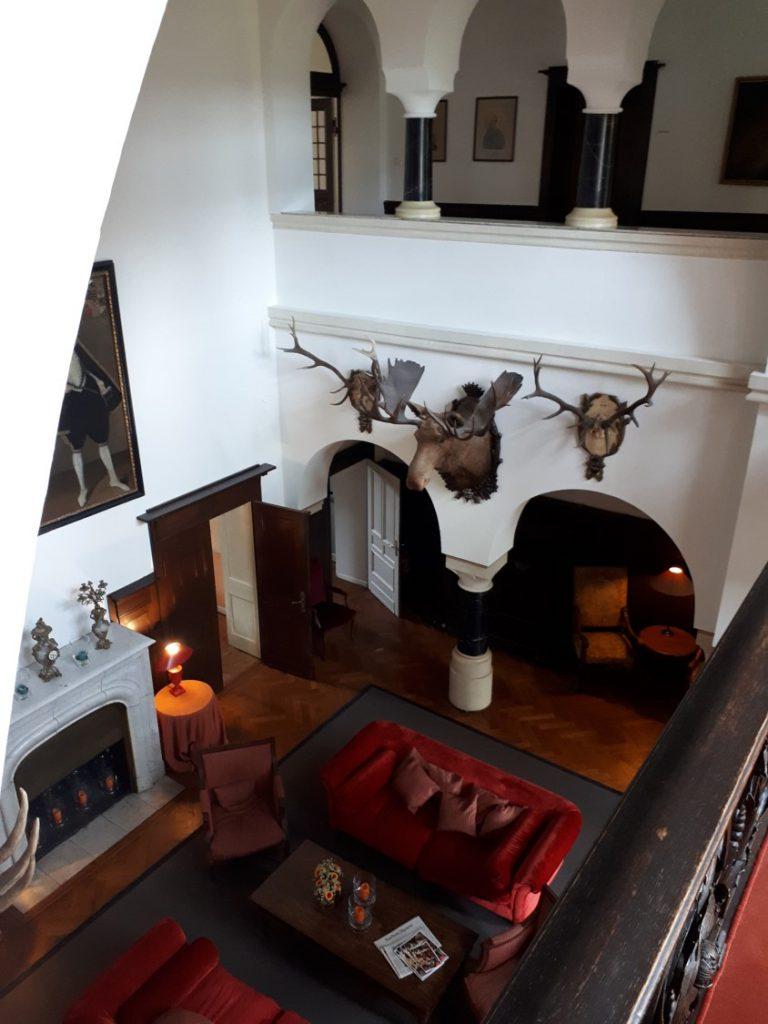 Blick von Galerie nach unten, Elchgeweihe, rote Samtsofas, großer Kamin