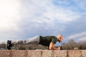 Mann in Sportkleidung macht Planken-Übung auf Mauer