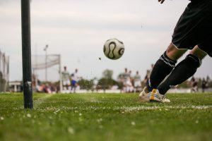 Fußball, Beine eines Spielers in schwarzen Strümpfen