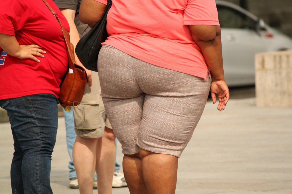 Adipäse Frau in eng sitzender beiger Hose und rosa T-Shirt von hinten