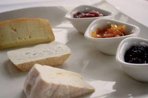 Käseplatte, drei Stück Käse, Schälchen mit Saucen und Fruchtzubereitungen