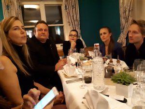 Menschen am Tisch, vorne links Frau mit langen blonden Haaren.