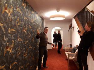Flur, links Wand mit Tapete, auf der Fasanen zu sehen sind, Blogger fotografieren sich gegenseitig