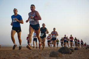 Reihe Männer beim Dauerlauf, in Sportkleidung und mit Startnummern