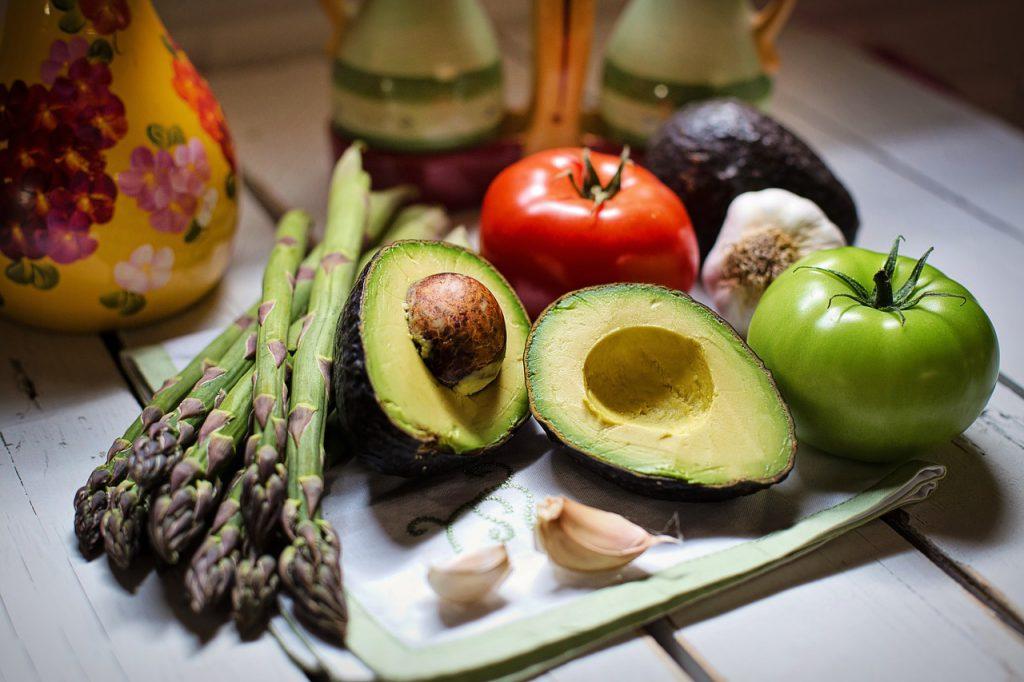 Nahaufnahme von Avocados, aufgeschnitten, Spargel, Tomaten und Knoblauchzehen