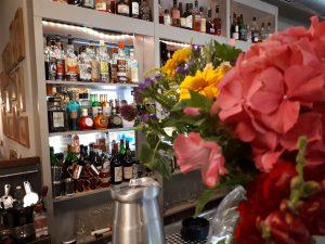 Bar im Hintergrund mit div. Edelspirtuosen, im Vordergrund Blumenstrauß