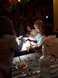Mann und Frau am Tisch, es ist dunkel, sie beleuchten einen Teller mit Handlampe und fotografieren.