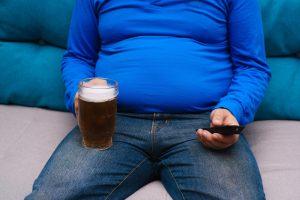 Fetter Mann in blauem T-Shirt mit Glas Bier und Fernbedienung in der Hand