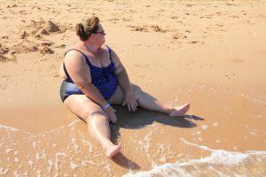 Dicke Frau in Badeanzug am Strand