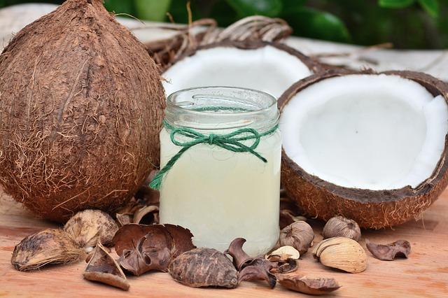 Kokosnuss ganz, zwei halbe Kokosnüsse und ein Glas mit reinem weißen Kokosnussfett