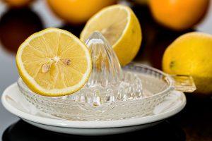 Gläserne Zitronenpresse mit zwei halben Zitronen