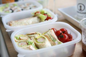 Weiße Plastikdose mit gerolltem Sandwich (Wrap)