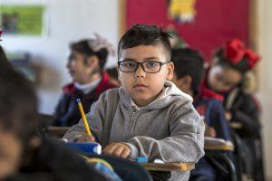 Junge, ca. 8 Jahre alt mit Brill und Kapuzenpulli in Klassenraum schreibt mit Bleistift