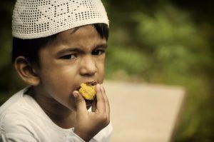 Kleiner Junge mit Gebetsmütze (weiß) steckt sich Kuchen in den Mund
