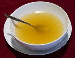 weißer Suppenteller mit klarer Brühe und einem Löffel